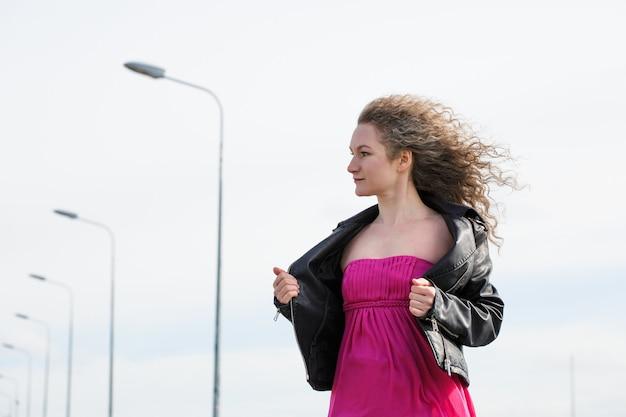 검은 가죽 재킷에 백인 곱슬 머리 여자와 등불과 흐린 하늘과 기둥의 핑크색 드레스