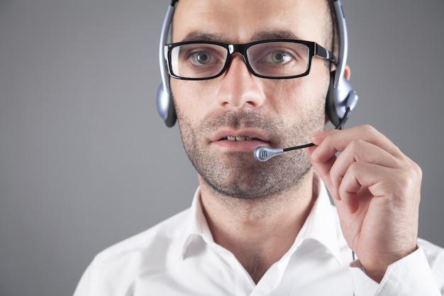 オフィスにヘッドセットを持っている白人のカスタマーサポートオペレーター。