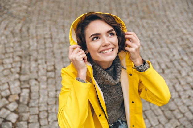 Caucasian cute female in yellow coat wearing hood on looking upwards rejoicing rainy weather while walking through city center