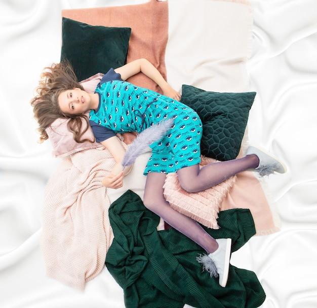 絹のようなベッドシーツでキングサイズのベッドで休んでいる白人のかわいい女の子。トップダウンビュー。