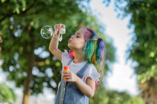 백인 귀여운 소녀가 공원에서 비누방울을 불고 있다. 선택적 포커스가 있는 이미지