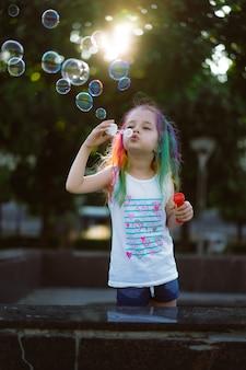 백인 귀여운 소녀가 공원에서 비눗방울을 불고 있다