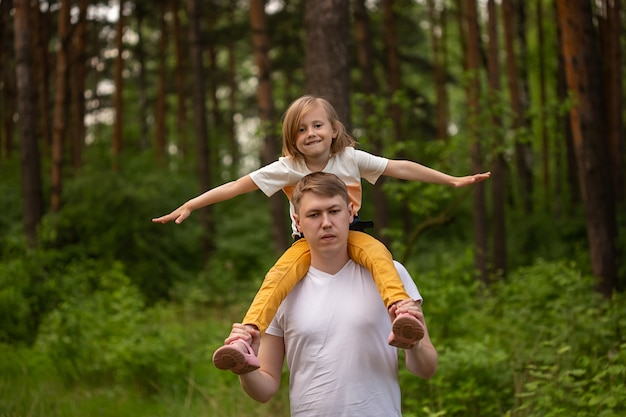 Кавказская милая маленькая девочка сидит на плечах отца в лесу. отец и дочь играют вместе, смеются и веселятся. концепция деятельности счастливой семьи