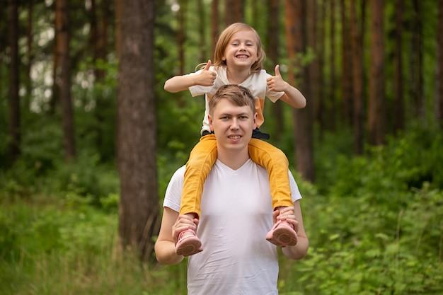 Кавказская милая маленькая девочка сидит на плечах отца в лесу