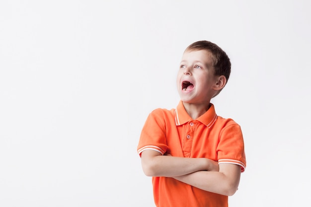 Caucasian cute shouting boy with open mouth and arm crossed standing over white background