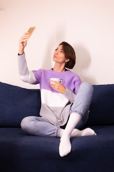 Caucasian cute woman blogger at home in warm purple sweater pullover take selfie in mirror on mobile phone
