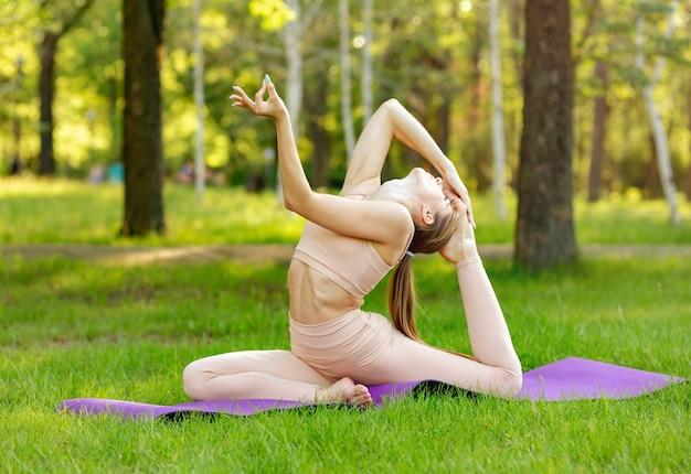 공원에서 요가 연습을 하 고 백인 귀여운 여자. 건강하고 차분합니다.