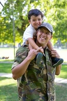 Figlio caucasico della holding del papà sul collo e sul sorridere. felice ragazzo carino che abbraccia il padre in uniforme militare. adorabile bambino che cammina con il papà nel parco cittadino. ricongiungimento familiare, paternità e concetto di ritorno a casa