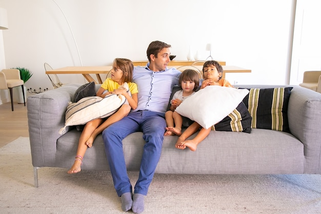 Caucasian dad sitting on sofa and embracing cute kids. loving middle-aged father relaxing with adorable children on coach in living room and talking. childhood, family time and fatherhood concept