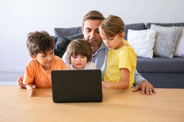 Papà caucasico che guarda film tramite laptop con i bambini. padre felice seduto a tavola con bambini adorabili. ragazzi premurosi svegli e ragazza bionda che esaminano schermo. infanzia e concetto di tecnologia digitale