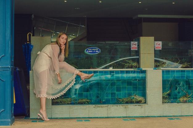 Caucasian dark blond model posing in a transparent chiffon cream dress near the aquarium with king lobsters in pattaya, thailand.