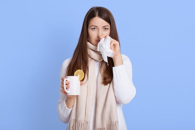 Кавказская темноволосая женщина в повседневной одежде и шарфе стоит с чашкой чая в руках