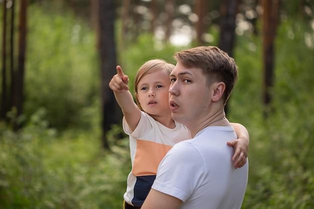 Кавказская дочка в папиной объятиях показывает пальцем в сторону в лесу