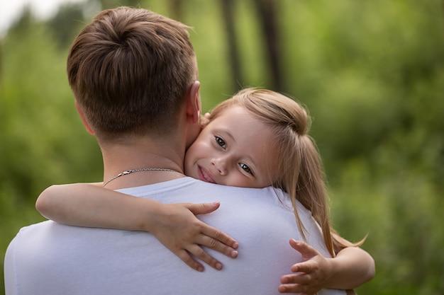 Кавказская дочь на руках у папы и обнимает его, глядя в камеру в лесу. отец и дочь играют вместе, смеются и веселятся. концепция деятельности счастливой семьи