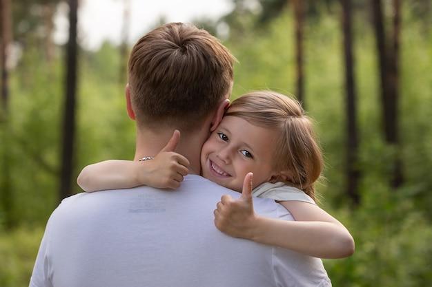 Кавказская дочка на руках у папы и обнимает его, глядя в камеру
