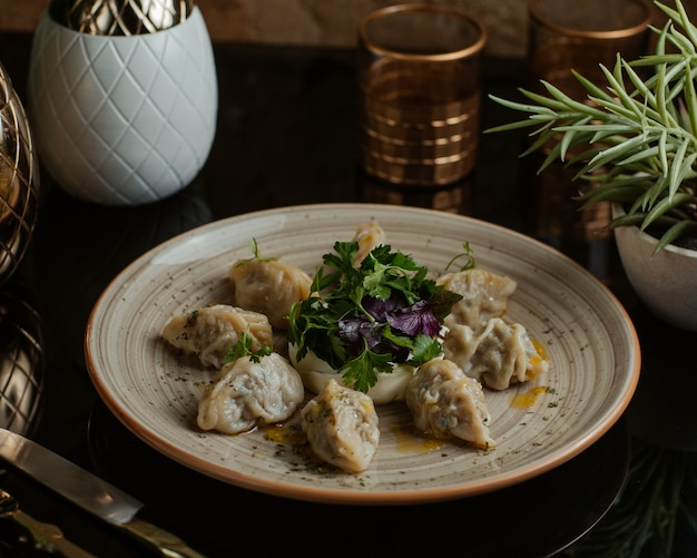 Кавказская вкусная еда хинкали, хингал, прекрасно приготовленный и подается со свежей петрушкой и красными листьями базилики