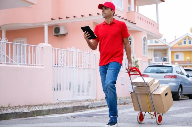 Fattorino caucasico con ruote carrello con scatole di cartone e tenendo la compressa. corriere professionale che cammina all'aperto e consegna l'ordine.
