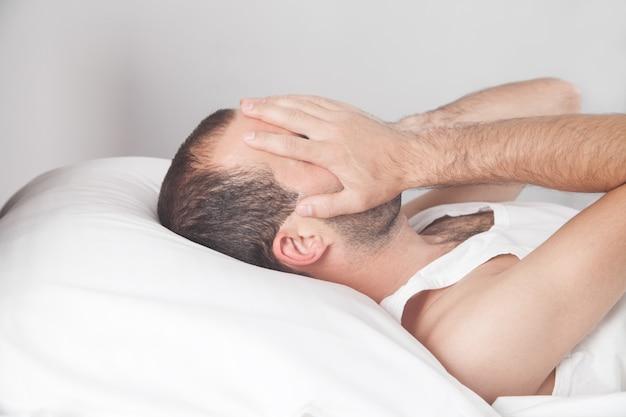 백인 우울한 남자가 자신의 침대에 누워 얼굴을 덮고
