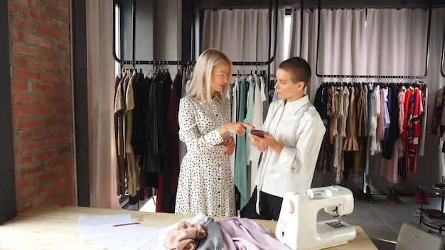 Caucasian designer discusses with a young woman the design of a dress, clothing