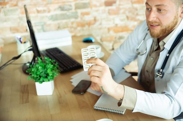 Кавказский врач консультирует пациента, объясняет рецепт лекарства, работает в кабинете
