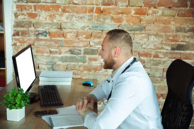 캐비닛에서 작업하는 약물에 대한 레시피를 설명하는 환자에 대한 백인 의사 컨설팅