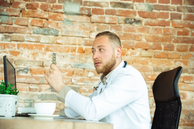Кавказский врач консультирует пациента, объясняя рецепт препарата, работающего в кабинете
