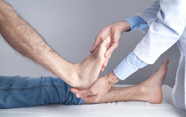 Caucasian doctor examining patient foot.