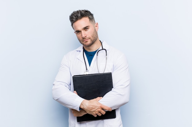 Caucasian doctor man holding a folder smiling confident with crossed arms