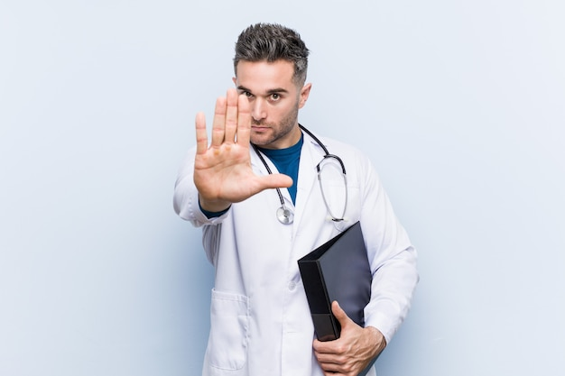 Caucasian doctor man holding a folder standing with outstretched hand showing stop sign, preventing you.