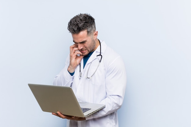 Caucasian doctor man holding a laptop biting fingernails, nervous and very anxious.