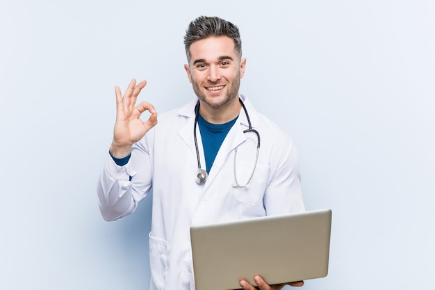 Caucasian doctor man holding a laptop cheerful and confident showing ok gesture.