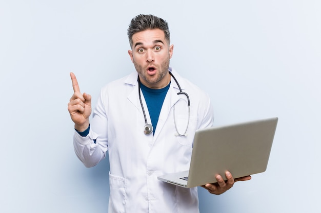 Caucasian doctor man holding a laptop having some great idea