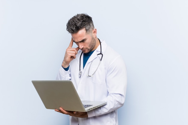 Caucasian doctor man holding a laptop pointing his temple with finger, thinking, focused on a task.