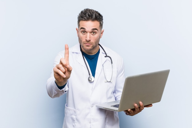 Caucasian doctor man holding a laptop showing number one with finger.