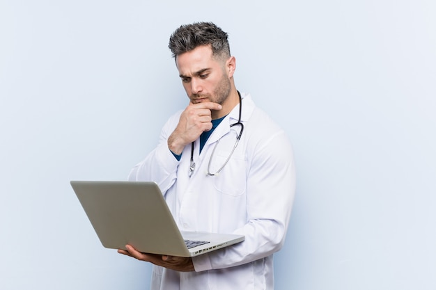 Caucasian doctor man holdinglaptop looking sideways with doubtful and skeptical expression.