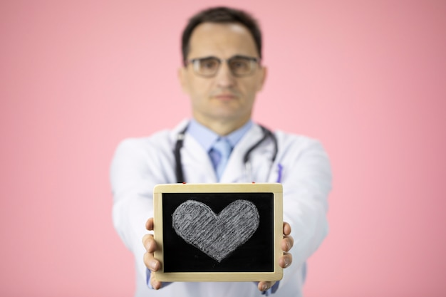 Caucasian doctor on pink holds heart drawing on outstretched hands