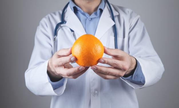 Кавказский врач показывает апельсин.