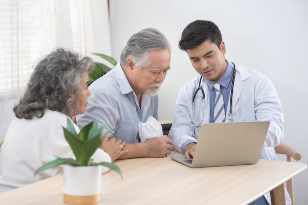 Caucasian doctor use laptop and talk with old asian male patient about disease symptom, elderly health check up at home.