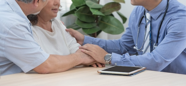 Caucasian doctor use tablet and talk with old asian female patient about disease symptom, elderly health check up at home.