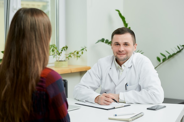 Caucasian doctor in white lab coat sitting at desk and listening to patient