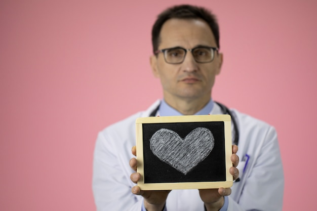 Caucasian doctor with stethoscope on pink holds a heart in his hands