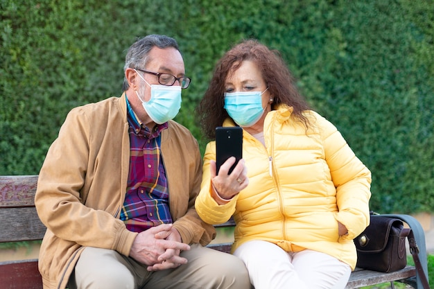 携帯電話を使う白人の老夫婦。彼らは屋外にいて、マスクを着用しています。