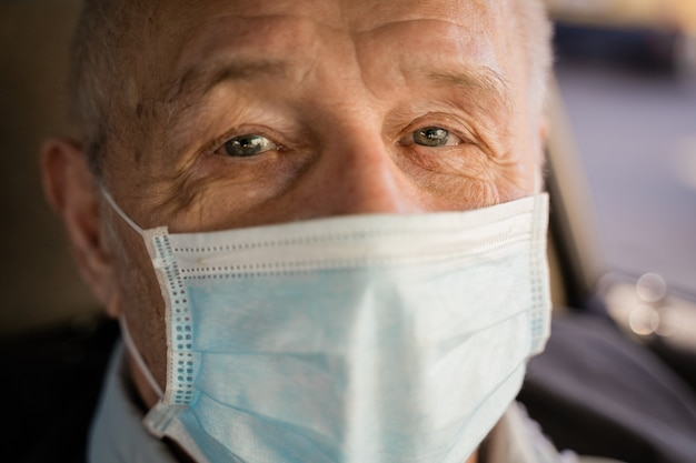 Caucasian elderly man close up portrait with face mask. covid-19 risk group. pandemic quarantine. high quality photo