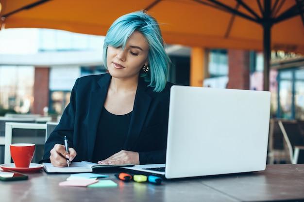 コンピューターを使用してコーヒーショップでいくつかのメモを作る青い髪の白人起業家