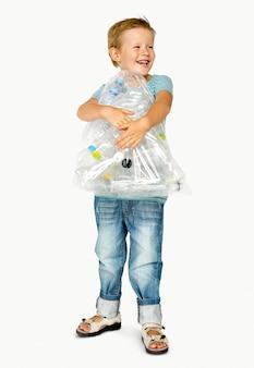 プラスチック製のボトルとバッグを保持している白人の民族少年