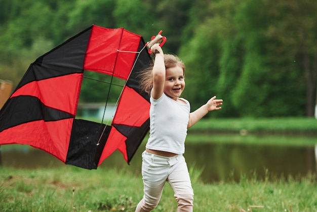 Caucasian ethnicity. positive female child running with red and black colored kite in hands outdoors
