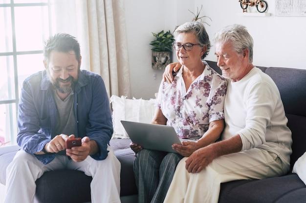 現代のテクノロジーデバイスを電話とラップトップコンピューターとして一緒に楽しんでいる自宅の白人家族-人々と代替のワークスタイルのオフィスまたはレジャーのオンライン活動