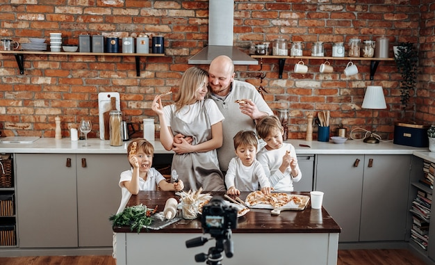 Caucasian family broadcasting their leisure activity and domestic lifestyle on tv. modern tv show of three little boys and their parents.