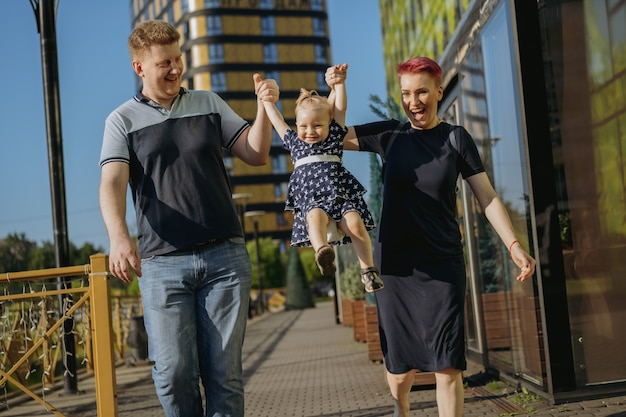 Caucasian family couple walking with baby girl lifting baby by hands. woman is happily laughing. high quality photo