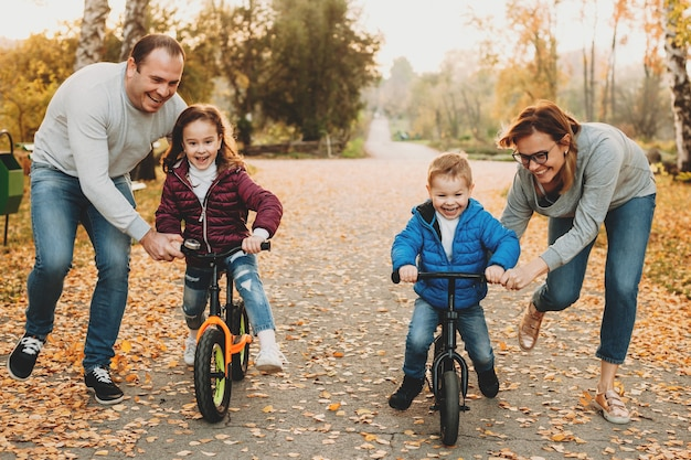 Caucasian family helping their kids to ride the bike